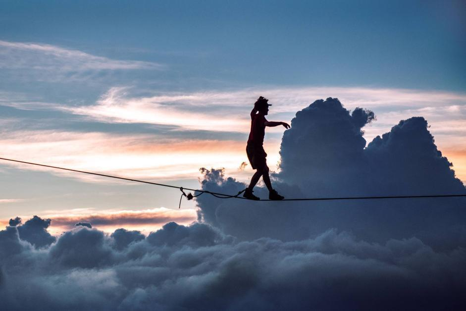 PIC BY SCOTT ROGERS / CATERS NEWS - (PICTURED: ANDY LEWIS HIGHLINING) - This fearless daredevil must have his head in the clouds - as he bravely edges across a highline a whopping 3000ft above the ground. Sky high Andy Lewis carefully moves forward inch by inch across the thin wire with the breathtaking backdrop of fluffy clouds and a magnificent glowing skyline behind him as the sun sets. In a different snap Andy, who has been slacklining and BASE jumping for the past 10 years, crosses another line WITHOUT a harness - and only water and rocks below him if he falls. The incredible images were taken this year on a trip to Brazil with friends who call themselves the Moab Monkeys - after the famous Utah desert, home to the some of the worlds top slackliners. SEE CATERS COPY